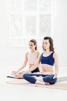 Jonge vrouwen doen yoga-oefeningen