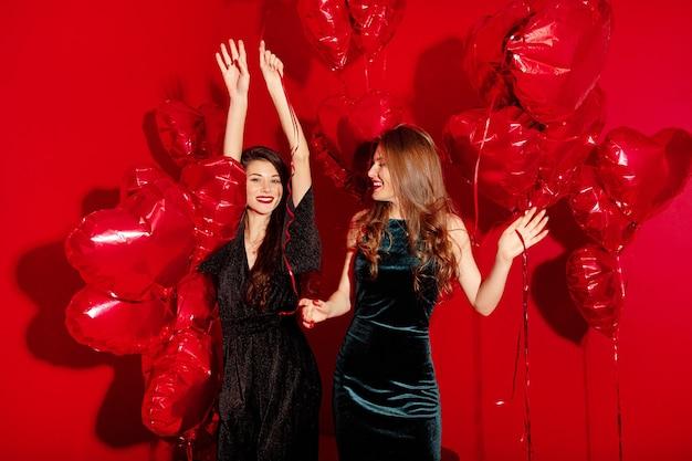 Jonge vrouwen feesten met hartvormige ballonnen voor valentijnsdag