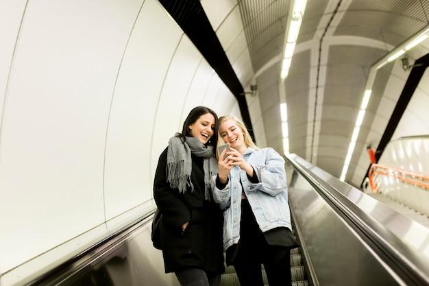 Jonge vrouwen gebruiken roltrappen en gebruiken een mobiele telefoon