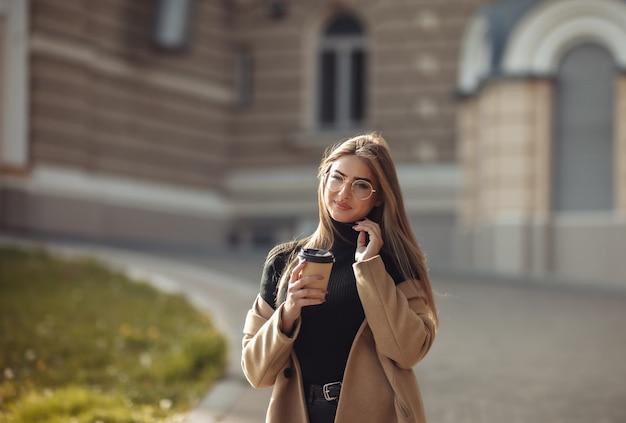 Jonge vrouwen gekleed in een stijlvolle jas drinken koffie op een achtergrond van stedelijke architectuur