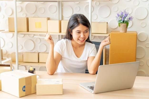 Jonge vrouwen gelukkig na nieuwe bestelling van klant, ondernemer thuis