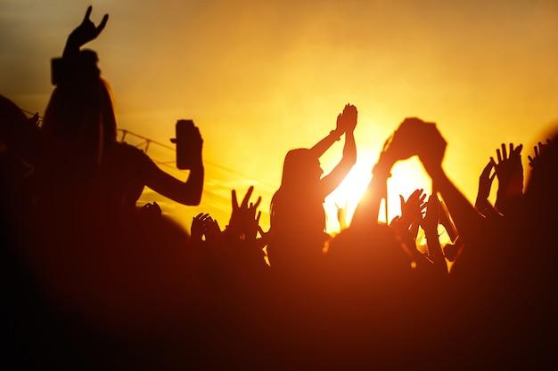 Jonge vrouwen genieten van een rockconcert silhouet op zonsondergang handen omhoog op openair