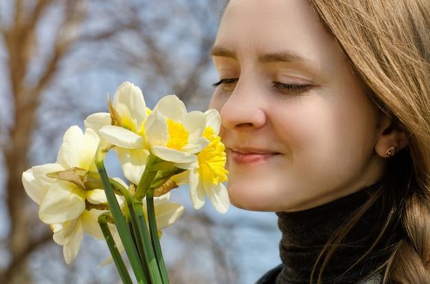 Jonge vrouwen genieten van het boeket van narcissen, close-up