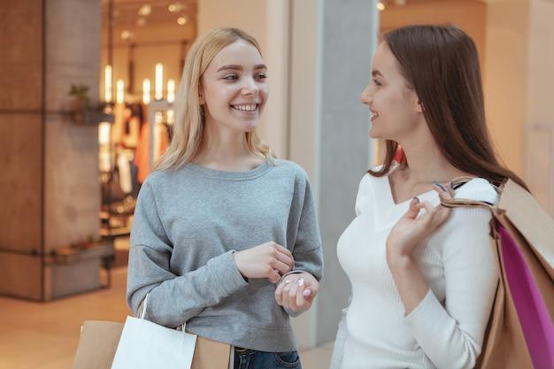Jonge vrouwen genieten van winkelen samen in het winkelcentrum