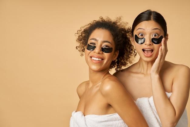 Jonge vrouwen gewikkeld in handdoeken poseren met aangebrachte zwarte hydrogel onder ooglapjes op de gezichtshuid