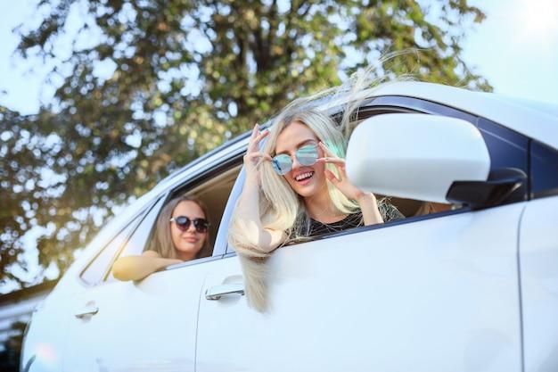 Jonge vrouwen in de auto glimlachen
