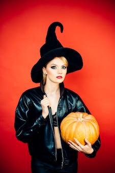 Jonge vrouwen in de kostuums van zwarte heksenhalloween op partij over rode muur. heks poseren met pompoen.