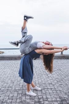 Jonge vrouwen in evenwicht brengende vriend bij haar die zich dichtbij het overzees bevinden