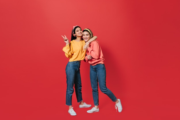 Jonge vrouwen in goede stemming tonen vredesteken en poseren op rode muur