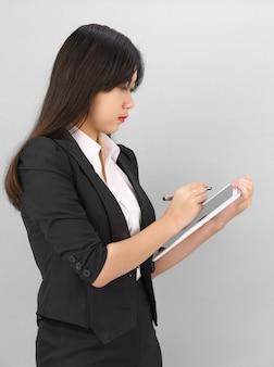 Jonge vrouwen in kostuum die haar digitale tablet gebruiken die zich tegen grijze achtergrond bevindt