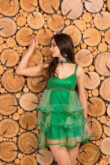 Jonge vrouwen in sexy kerstboomkostuum op houten achtergrond, studio