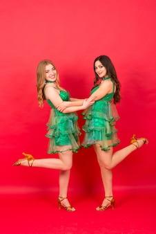 Jonge vrouwen in sexy kerstboomkostuum op rode muur in studio
