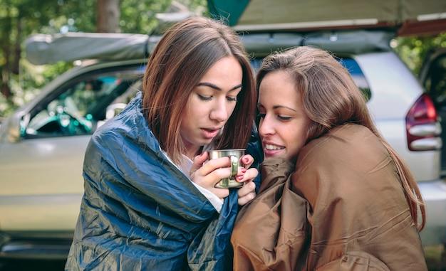 Jonge vrouwen in slaapzakken met kop warme koffie in een koude ochtend buitenshuis