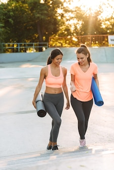 Jonge vrouwen in sportkleding glimlachend en wandelen op sportveld met fitnessmatten