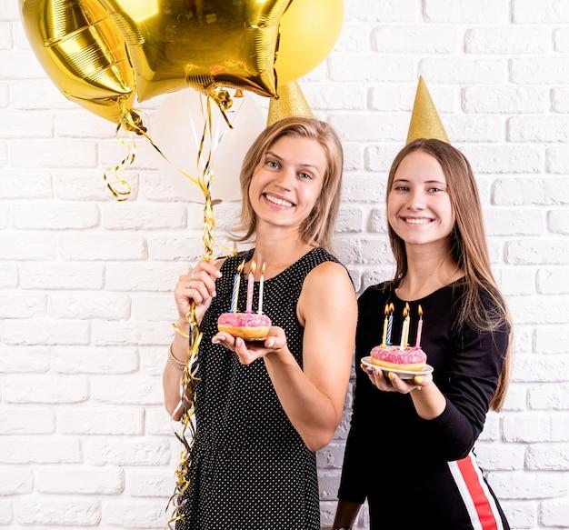 Jonge vrouwen in verjaardagshoeden die verjaardag vieren