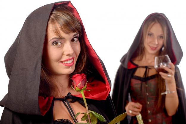 Jonge vrouwen in vermomming halloween met een glas bloed en een roos