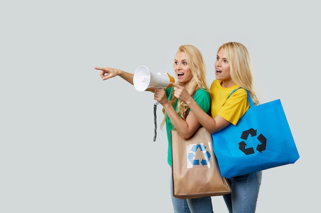 Jonge vrouwen in vrijetijdskleding houden ecologische gerecyclede boodschappentassen vast en schreeuwen in een megafoon om plastic afval te recyclen. wijs links naar lege ruimte voor tekst.