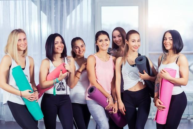 Jonge vrouwen in yogales glimlachen en praten na fitnessoefening met yogamatten