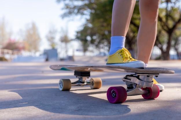 Jonge vrouwen lopen op zijweg in de buurt van tropisch strand met skate board.