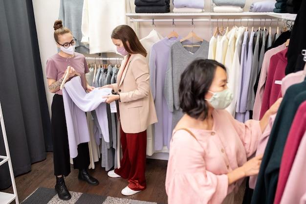 Jonge vrouwen met beschermende maskers die winkelen in de winkel tijdens pandemie