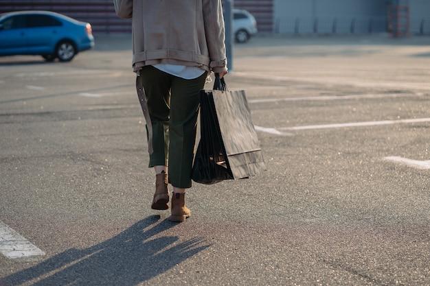 Jonge vrouwen met boodschappentassen die op straat lopen.