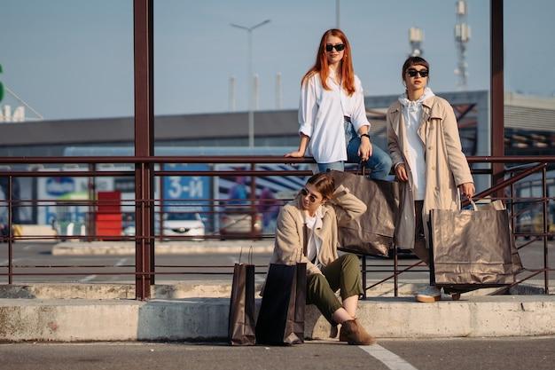 Jonge vrouwen met boodschappentassen op een bushalte