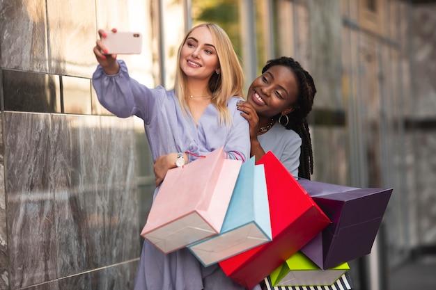 Jonge vrouwen met boodschappentassen selfie nemen