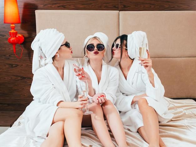 Jonge vrouwen met champagne pruilende lippen. zonnebrillen, badjassen en tulbanden aan. blote benen schoonheid.