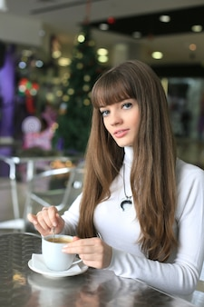 Jonge vrouwen met een kopje koffie in een supermarkt op de achtergrond van de kerstboom