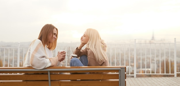 Jonge vrouwen met koffie die op bank spreken