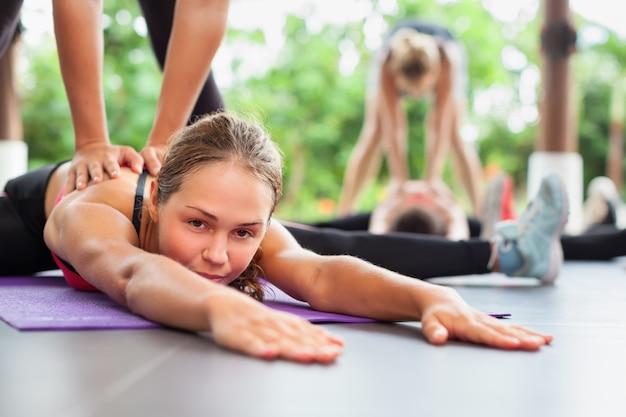 Jonge vrouwen met slanke lichamen die zich uitstrekt op de mat tijdens fitnesslessen