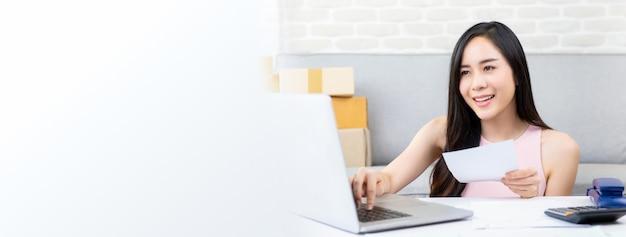 Jonge vrouwen online verkoper die aan laptop computer werkt