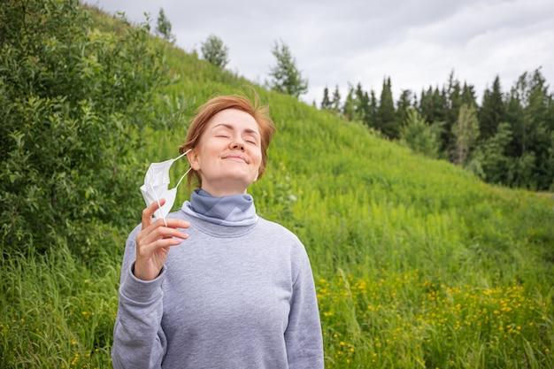 Jonge vrouwen opstijgen een wegwerp medisch masker in een park op een achtergrond van een heuvel met gras en bomen.