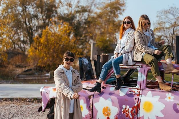 Jonge vrouwen poseren in de buurt van een oude versierde auto