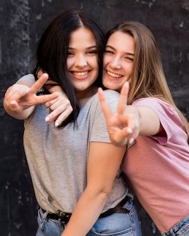 Jonge vrouwen poseren met vredesteken