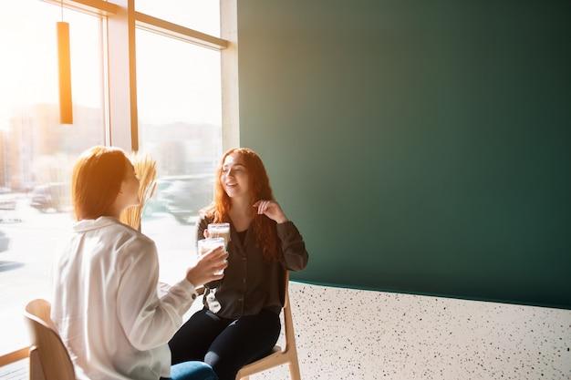 Jonge vrouwen praten in een café. vrouwelijke modellen die koffie drinken en lachen.