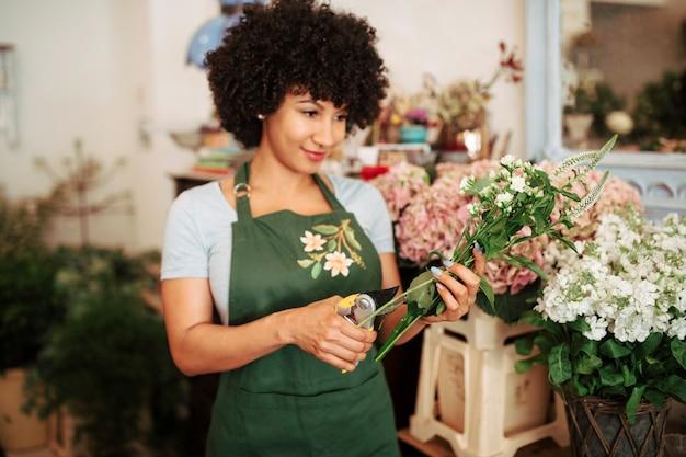 Jonge vrouwen scherpe stam van bloemen met snoeischaar in bloemwinkel