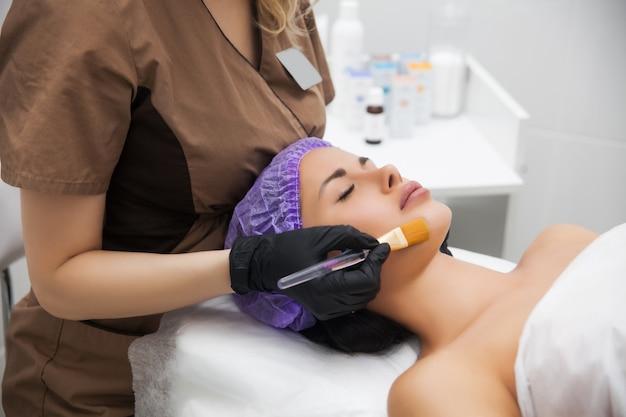 Jonge vrouwen schoonmakende gezichtshuid in schoonheidssalon. gezichts retinolbehandeling van de borstelschil. schoonheid vrouw peeling procedure. cosmetologie jong meisje therapie. hyaluronzuur.
