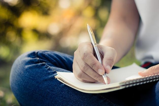 Jonge vrouwen schrijven op notebook in park, onderwijs en kennis