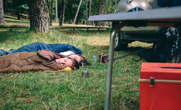 Jonge vrouwen slapen in de natuur in slaapzakken over het gras op de camping