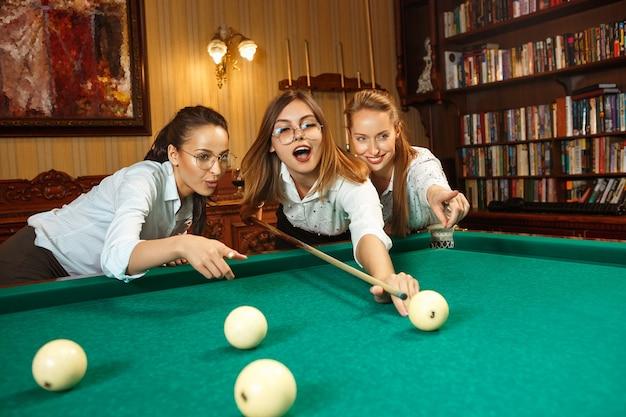 Jonge vrouwen spelen biljart op kantoor na het werk.