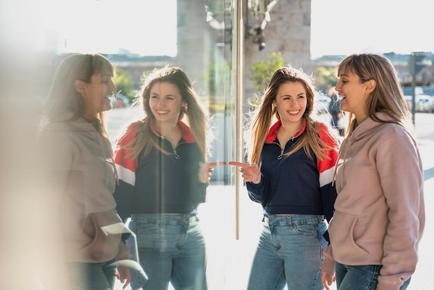Jonge vrouwen spiegelen zich voorstellen in venster
