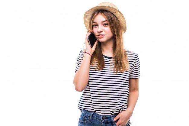 Jonge vrouwen sprekende telefoon die op witte muur wordt geïsoleerd