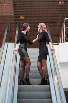 Jonge vrouwen staan op de trappen van de roltrap in het zakencentrum