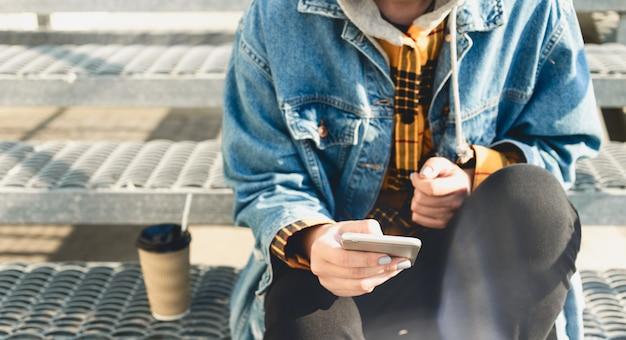 Jonge vrouwen texting zitting op de stadsstappen