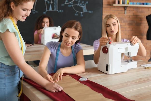Jonge vrouwen tijdens kleermakersles in atelier