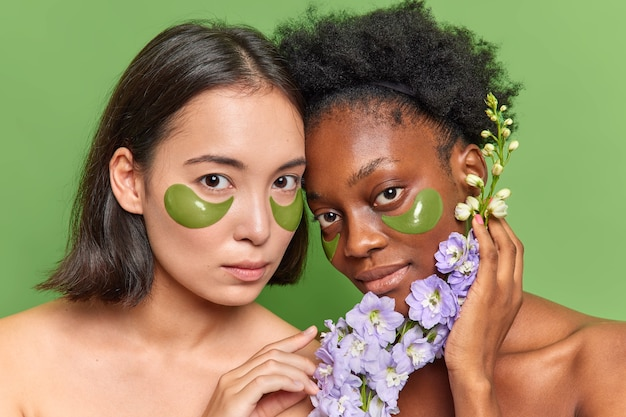Jonge vrouwen van gemengd ras ondergaan schoonheidsprocedures, brengen hydrogelpleisters onder de ogen aan, houden bloemkruiden vast