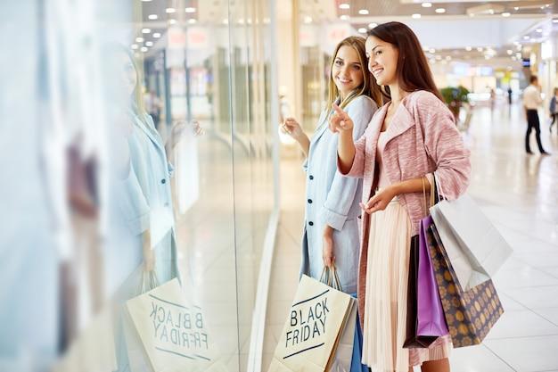 Jonge vrouwen venster winkelen in winkelcentrum