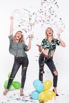 Jonge vrouwen vieren met confetti