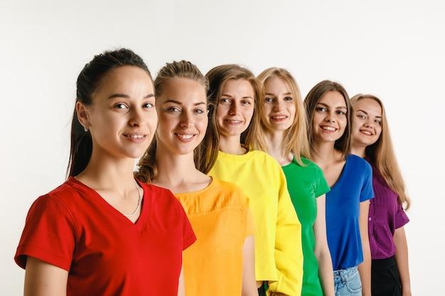 Jonge vrouwen weared in lgbt-vlagkleuren die op witte muur worden geïsoleerd. blanke vrouwelijke modellen in heldere overhemden. kijk gelukkig, lachend. vertrouw op lgbt-trots, mensenrechten, keuzevrijheid.